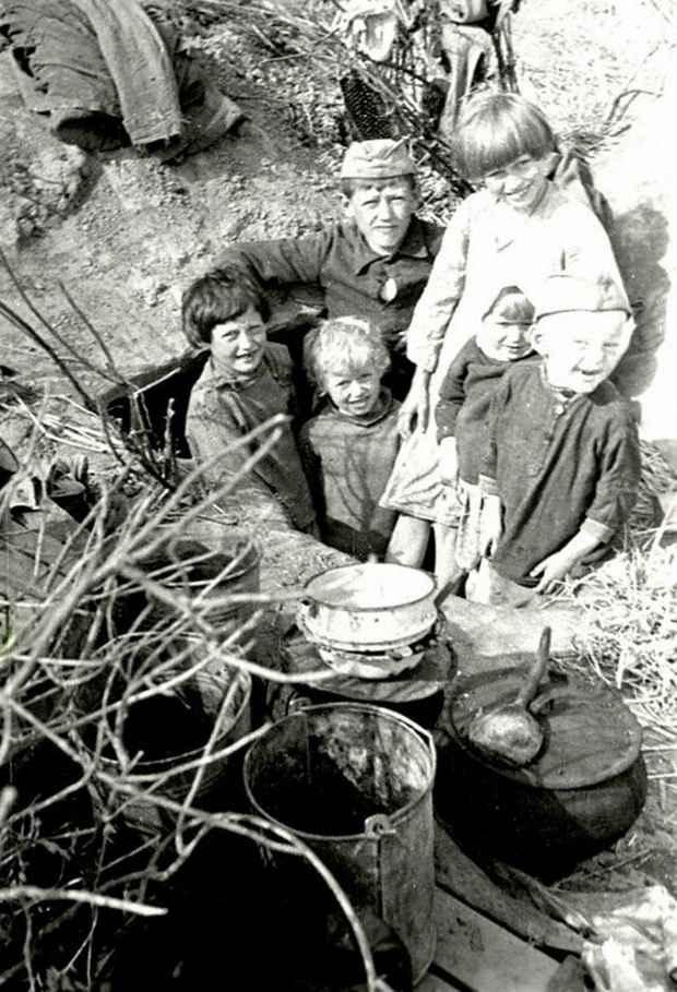 Дети колхозников одной из деревень Калининской области в лесу у землянки, где они жили в дни оккупации. 1942 г. Калининская область