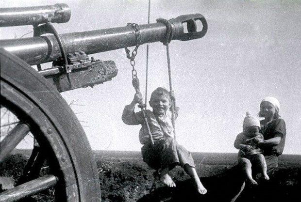 Мальчик качается на качелях, подвешенных на дуло брошенного немцами орудия. Рядом девочка с маленьким ребенком на коленях. 1944 г. Украина, Николаевская область.